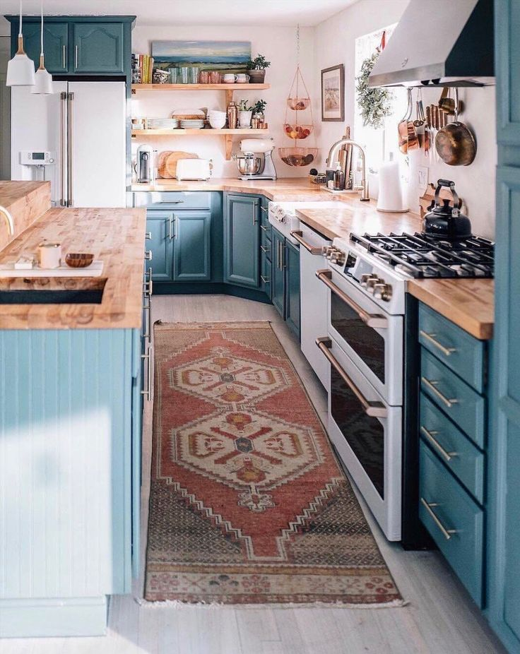 Love the colored cabinets, white walls, and wood c…