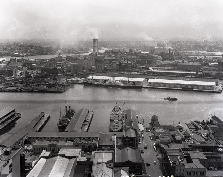 View looking west from AWA Tower in York Street down Erskine Street to ferry wharf and ships at finger wharves on city side and Pyrmont side. Chimneys of Pyrmont Power Station at centre rear. Photographer Allan A. Hedges. Photo courtesy of City of Sydney Archives.    **