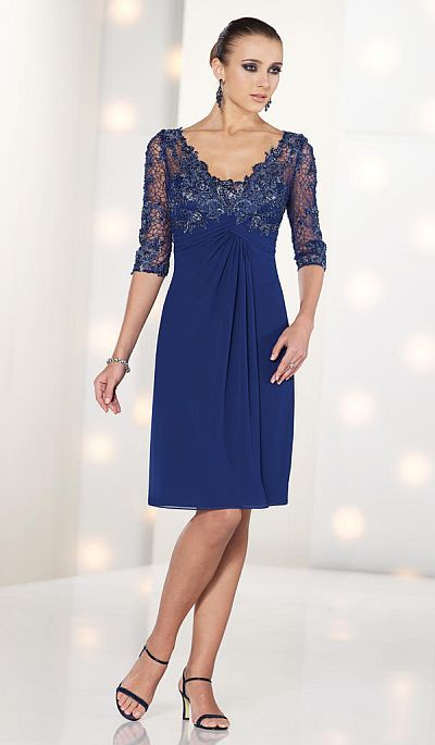 Chiffon knee-length A-line dress with hand-beaded lace three-quarter length sleeves and front and back V-neckline bodice, ruched Empire waistline, cascading back ruffle, front gathered skirt.