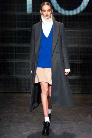 「DKNY」カラーとシルエットで魅せるスクールガールスタイル。 「DKNY」では、スクールガールのユニフォームを彷彿とさせるルックがランウェイを彩った。トップバッターを務めたのは、多くのデザイナーからのラブコールが止まないマールチェ・フェホーフ。エレクトリックブルーのVネックセーターにベージュのスカート、グレーのロングコート、白ソックスのコーディネートで登場した。その後もレッドのハイネックのトップスやターコイズのリブニットセーターなどポップなカラーを採用したアイテムが続々。シルバーのグリッターをラペルに施したキャメル色のアウターや、ビジューをあしらった黒のセットアップやブルゾン、バイカラーのアシンメトリーなワンピースなど、ツイストを効かせたコンサバで正統派なアイテムも提案した。