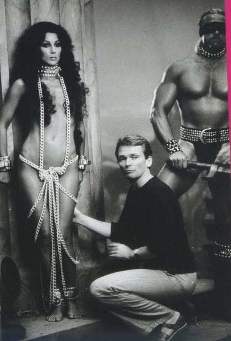 "Masculine Man: Thonged bodyguard looks tough while Bob Mackie styles Cher for the ""Prisoner"" album photoshoot, 1979."