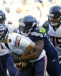 Seattle Seahawks defensive end Cliff Avril (56) tackles Chicago Bears quarterback Jimmy Clausen (8) as Bears' Kyle Long (75) looks on in the second half of an NFL football game, Sunday, Sept. 27, 2015, in Seattle. The Seahawks beat the Bears 26-0. (AP Photo/Elaine Thompson)