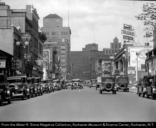Westerly view of East Avenue looking towards Main Street. Business include: the Sergeant Motor Co., a Ford dealership located at 200 East Ave; The Parrot Grill Co., a restaurant at 178 East Avenue; Union Oil Works, a gasoline station at 178 East Ave; and the L. W. Sage & Co., an automobile parts and utility store at 370 East Ave. Just beyond it is a Western Auto Supply Co. sign. To the left is the Cutler Building and its tower.