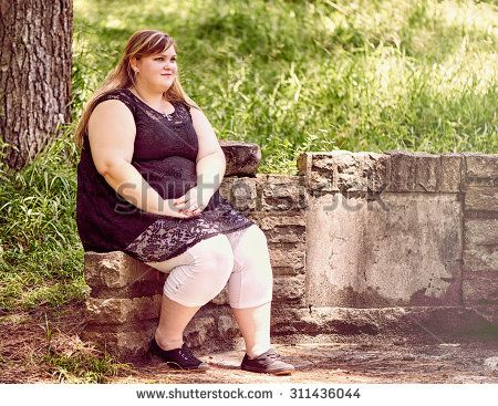 Beautiful confident young blond caucasian teenager sitting on a stone wall in a forrest with copy space on the right of the image