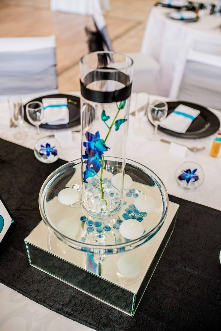 Monte Vista Venue blue and black centerpiece with a blue orchid in a vase with a clear jelly babies and a black ribbon around the top, in a glass bowl with blue pebbles and 4 white floating candles in, all on a mirror box surrounded by 4 small bowls with clear jelly babies and a blue orchid in.