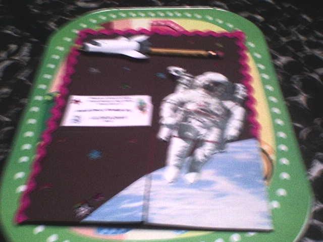 Un astronauta en la luna, decorado con estrellas alrededor y una nave espacial, las figuras se hacen sobre relieve