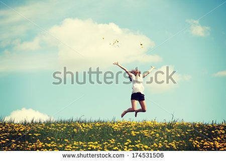 Happy woman jumping on blossom meadow. Beautiful day on field. - stock photo