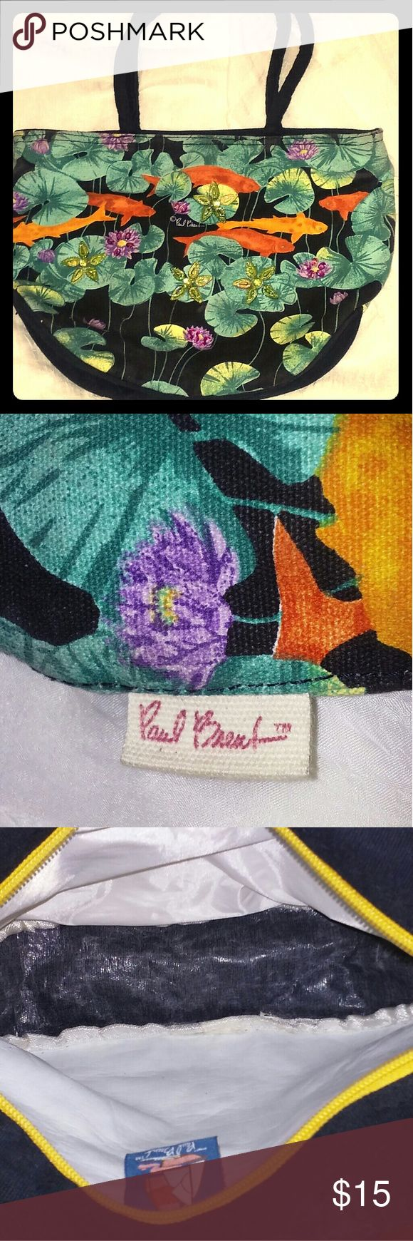"""Paul Brent handbag One of Paul Brent's fun totes just in time for spring. Orange Koi fish in a lily pond covers both front and back. Koi fish are a common symbol in both Chinese culture and feng shui. Ornamental green and purple Jewel flowers on the front. Inside is clean and material is canvas on one side and satin 'like' on the other. Has orange zipper to close bag. Minimal ware and tear. 14""""x3""""x10"""" = LxWxH Paul Brent  Bags Totes"""