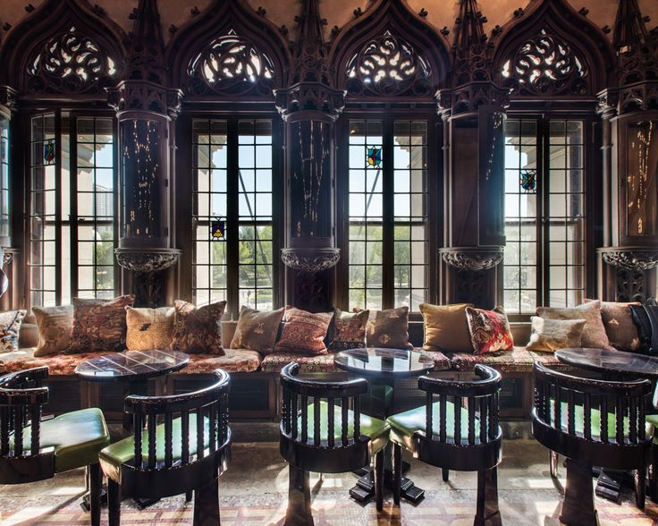 The new Chicago Athletic Association Hotel, overlooking Millennium park has a beautiful lounge area with Gothic style peak arch windows and wood detailing, a long window seat full of patterned pillows and circular back wooden chairs. Click through for more images of this fully restored Venetian Gothic building.