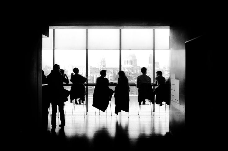 A black-and-white shot of people sitting on stools at a long table