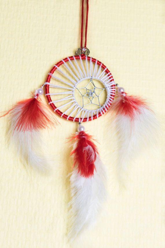 Un joli capteur de rêves aux couleurs de Noël !  Cet attrape-rêves bénéficie dun double tissage en forme déclipse et détoile, blanc et argent. Il se compose : - Anneau en acier 7.5 cm recouvert de fil de nylon, rouge - Anneau en acier 3.5 cm recouvert de fil de coton, blanc - Tissage fil de coton, blanc - Tissage fil acier, argenté - Perles de nacre 8mm, blanc - Perles acier, argent - Perles Acryliques 20mm, gris - Plumes, blanc et rouge  Un attrape-rêves qui décorera joliment votre maison…
