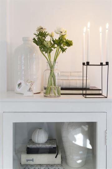 En bukett med vita ranunklar pryder ett vitmålat skåp i vardagsrummet. Ljusstake i svart med smala ljus från Madam Stoltz och vit urna från PB home.