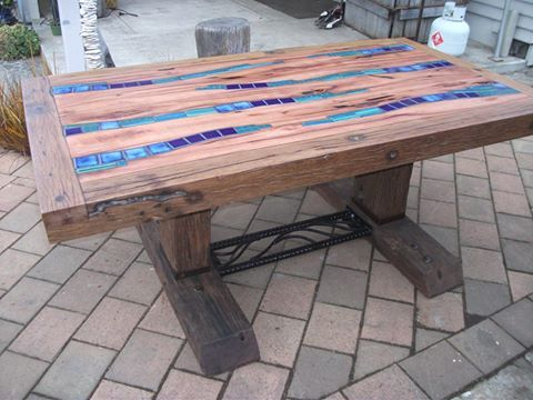 table made of recycled hard wood, with ceramic tile inlay, and reinforcing bar brace at bottom