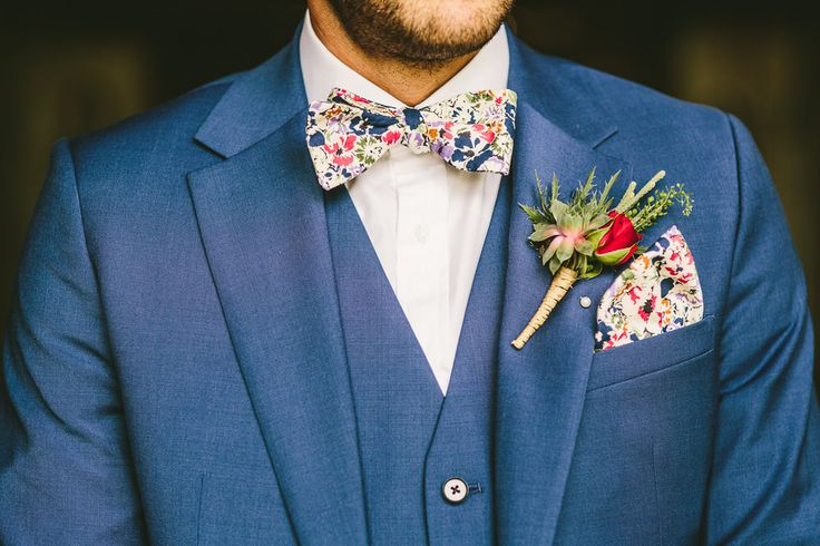 Weiss blue 3 piece suit, red rose buttonhole and floral bow tie and pocket square - Image by Samuel Docker Photography - Claire Pettibone lace dress in a rustic barn wedding in the Cotswolds with red bridesmaid dresses. Groom wears a Reiss Suit with floral bow tie and light up letters decoration.