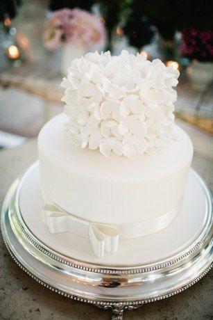 Torta de boda blanca decorada con cinta de satín y flores de azucar. #TortadeBoda