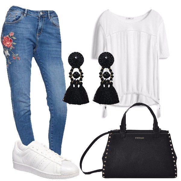 Outfit da giorno, composto da T-shirt bianca a maniche corte con scollo tondo abbinata ad un paio di jeans blu con rose ricamate e ad un paio di sneakers basse bianche in pelle, borsa a spalla nera con borchie in pelle. A completare il look orecchini pendenti neri con cristalli in tessuto.