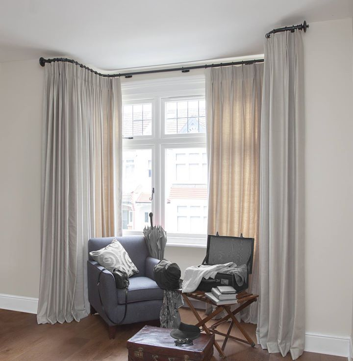 Bay window with neutral overlong curtains and a custom bent bay pole from The Bradley Collection. Pole in flint gloss with globe finials