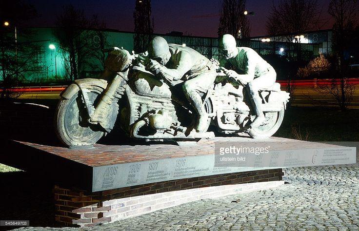 Nachtaufnahme der Motorrad-Skulptur vor den alten Messehallen, die dargestellten Motorradfahrer sind Ewald Kluge (DKW) und Ernst Henne (BMW)- 1998