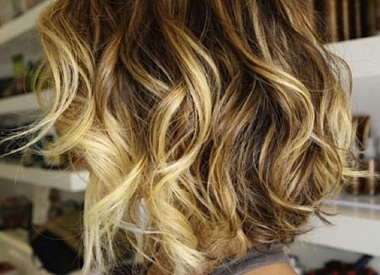 Short blonde hair with dark brown roots.