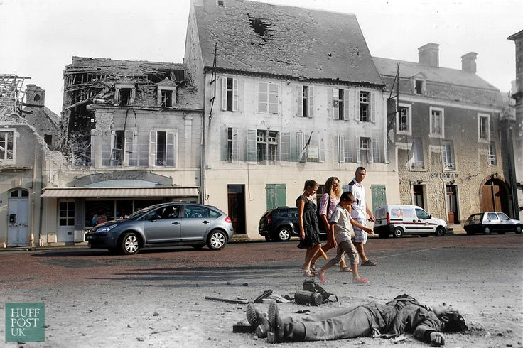D-Day Landing Sites Then And Now: 11 Striking Images That Bring The Past And Present Together - Tourists walk by where the body of a dead German soldier once lay in the main square of Place Du Marche in Trevieres after the town was taken by US troops who landed at nearby Omaha Beach in 1944.