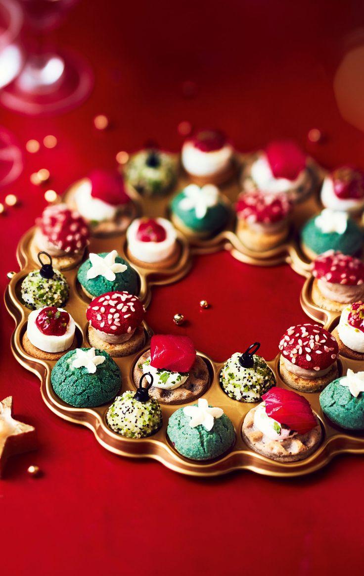 #MaTableAuSommet  Aussi décorative que délicieuse, cette couronne apéritive contient 28 pièces aux formes et couleurs de Noël ! Elles sont toutes garnies de produits d'exception : saumon fumé, brie à la truffe noire, Saint-Jacques ou bloc de foie gras.  #Noël #Repas #Apéritif #Chic #Dînatoire
