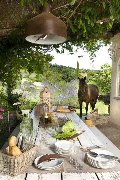 Il patio esterno ospita un'accogliente e raffinata zona pranzo dall'allure country chic