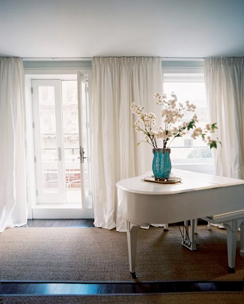 Living Room Photo - A wall of white curtains with a white piano atop a natural-fiber rug