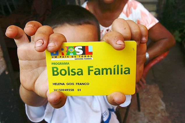 Família mostra cartão do benefício do Bolsa Família