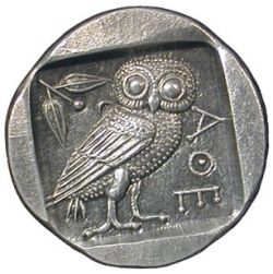 The photo depicts the Tetradrachm of Athens coin. On its one side the owl of Athens, with an olive sprig was carved. On the reverse side of this ancient coin there is a portrait of the goddess Athena, patron of ancient Athens, in helmet.