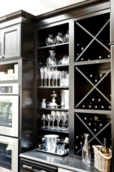 Suzie: Grothouse Lumber - Glossy black cabinets with built-in wine racks and mirrored backsplash.