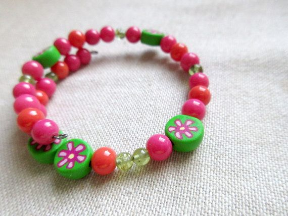 This sciart physics bracelet features G in pink, green, and orange beads, with handmade polymer clay flower beads as spacers in between digits.