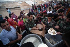 Syrian-Kurdish refugee families queue to get food at the Quru Gusik refugee camp, 20 kilometres east of Arbil, the capital of the autonomous Kurdish region of northern Iraq, on August 27, 2013.