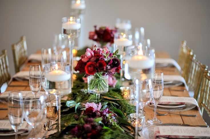 Pallet wood table with a greenery runner with purple and red flowers. Glass stemmed candle holders with gold Tiffany chairs and glass underplates.