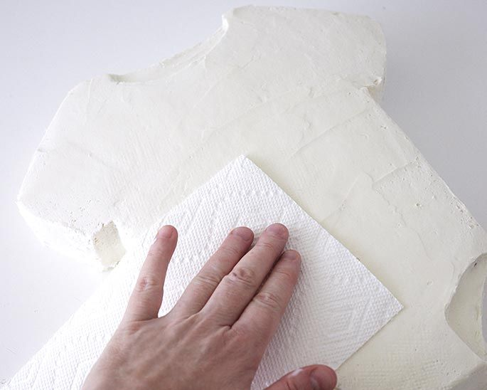 Smoothing a cake with paper towel