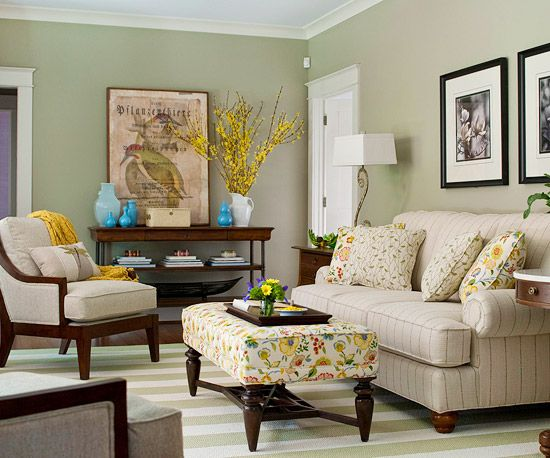 Green Living ~~ A soft green hue infuses this living space with vitality and elegance. The gentle green walls function as a neutral backdrop for a variety of soft patterns and bold colors found on the sofa, ottoman, and throw pillows. Vases filled with fresh flowers are natural accents for the earthy green hue.