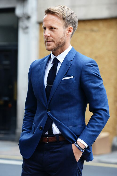 Blue blazer, shite shirt, blue trousers, white pocket square, blue tie, brown belt, tie clip