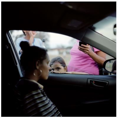 "This photograph is apart of Raphaela Rosella's series ""You didn't take away my future. You gave me a new one"". For me I really like how in this particular photo there is a child peering through the car window, and how a presumably pregnant teenager is in the car looking ahead while people surround the car. It looks like there are adults watching the car leave with the teenager which relates to the concept of the series about a teen mum being an outsider to society."