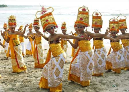 Balinese girls in traditional dress dance on Kuta beach during a Melasti purification ceremony - Bali, Indonesia.