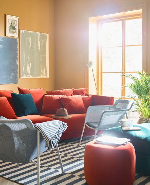 In een felgekleurde woonkamer met okergele muren staan een rode sofa en fauteuils