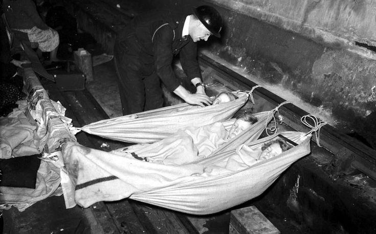 An air warden checks on children sleeping in hammocks in a London Underground station during the Blitz.
