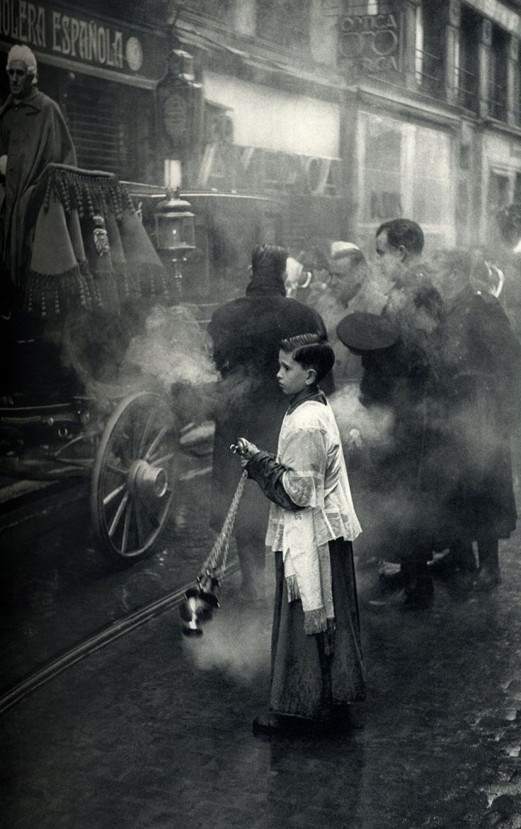 "artemisdreaming: Henri Cartier-Bresson . Madrid, 1953. ""The priest steps up to bring the Blessed Sacrament to an ill person during a procession, accompanied by military music near the Puerta del Sol."" Artemis: Another from him that every time I see it I wonder. Procession? Military music? Why? Ill? Who? :D"