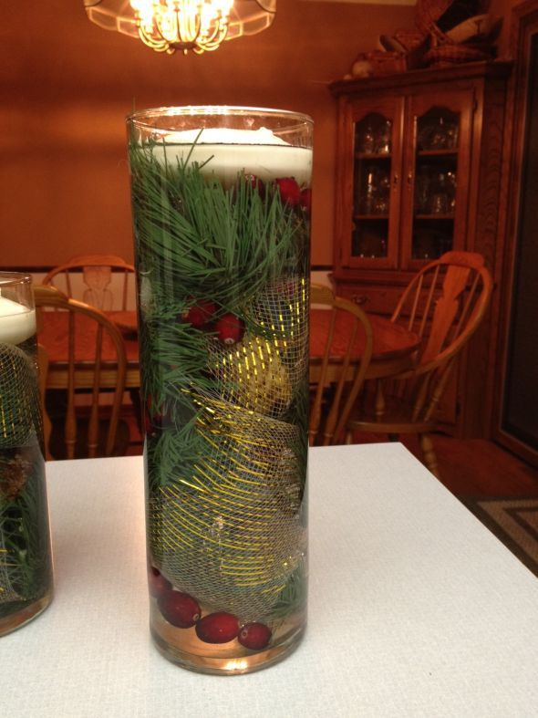 Pine needles submerged in water with floating candle