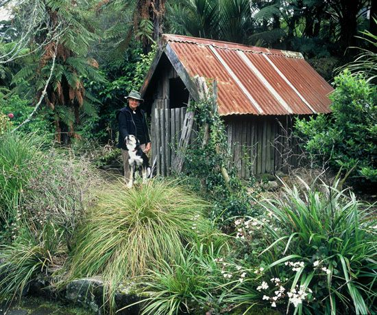 Te Kainga Marire - Owner, Valda, family dog Del, in front of rustic woodshed.
