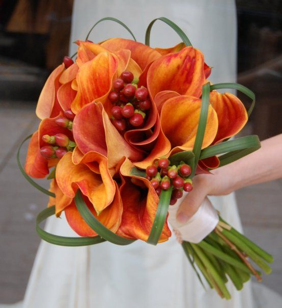The flowers in this photo form a lovely orange calla lily wedding bouquet with beargrass accents. Designed by Monday Morning Flower & Balloon Company, a Princeton New Jersey florist.