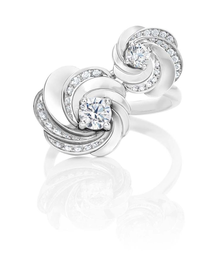 De Beers Aria earrings in white gold set with pavé diamonds surrounding a central brilliant-cut diamond.
