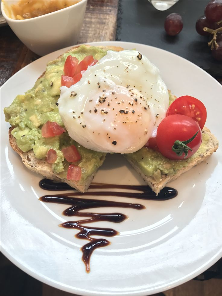 Smashed avocado with poached eggs and squishy vine tomato