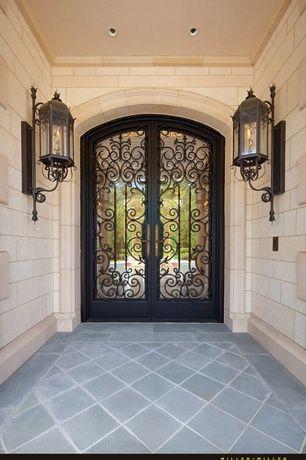 Mediterranean Front Door with French doors, Antiqued black wall mount lantern, exterior stone floors, Pathway
