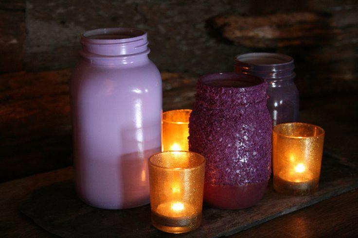 Slate base. 3 purple mason jars. 3 gold, glitter votive candle holders. Simple arrangement needed for each mason jar.