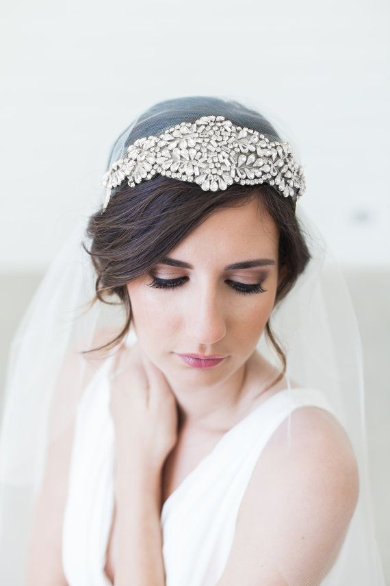 This delicate, Art Deco inspired veil is a modern take on the glamorous era where the Juliet Cap Veil became a wedding trend. It is made of soft, high quality tulle in several color options. A gorgeous, removable headband is composed of cascading leaves on each side and a large applique of clear rhinestones with silver-tone settings and glass beads in a lovely Art Deco pattern, The headband can be worn either across the forehead or at the crown - styling is easy and completely up to you. It…