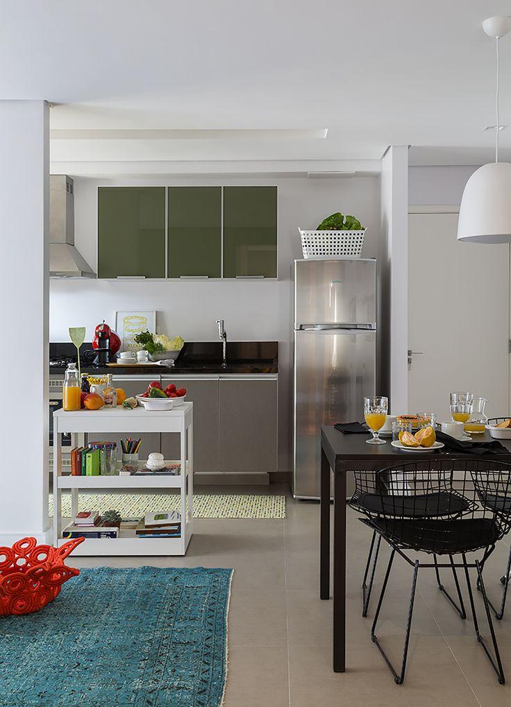 Seguindo o conceito pop e colorido, a cozinha recebeu armários verdes com acabamento brilhante. Já a bancada cinza fosca quebra o aspecto vibrante e deixa o ambiente mais sóbrio.